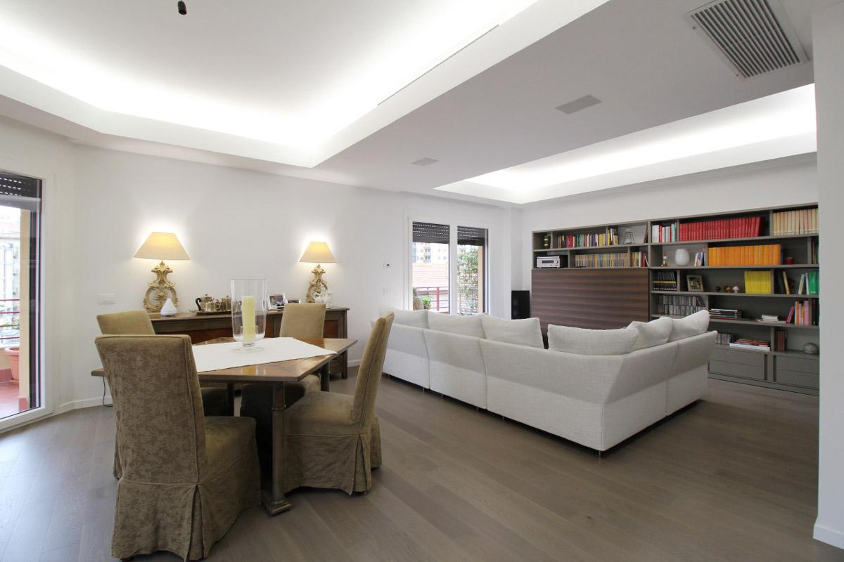 Tavolo quadrato con 4 sedie attorno di una sala da pranzo integrata in un open space con il soggiorno
