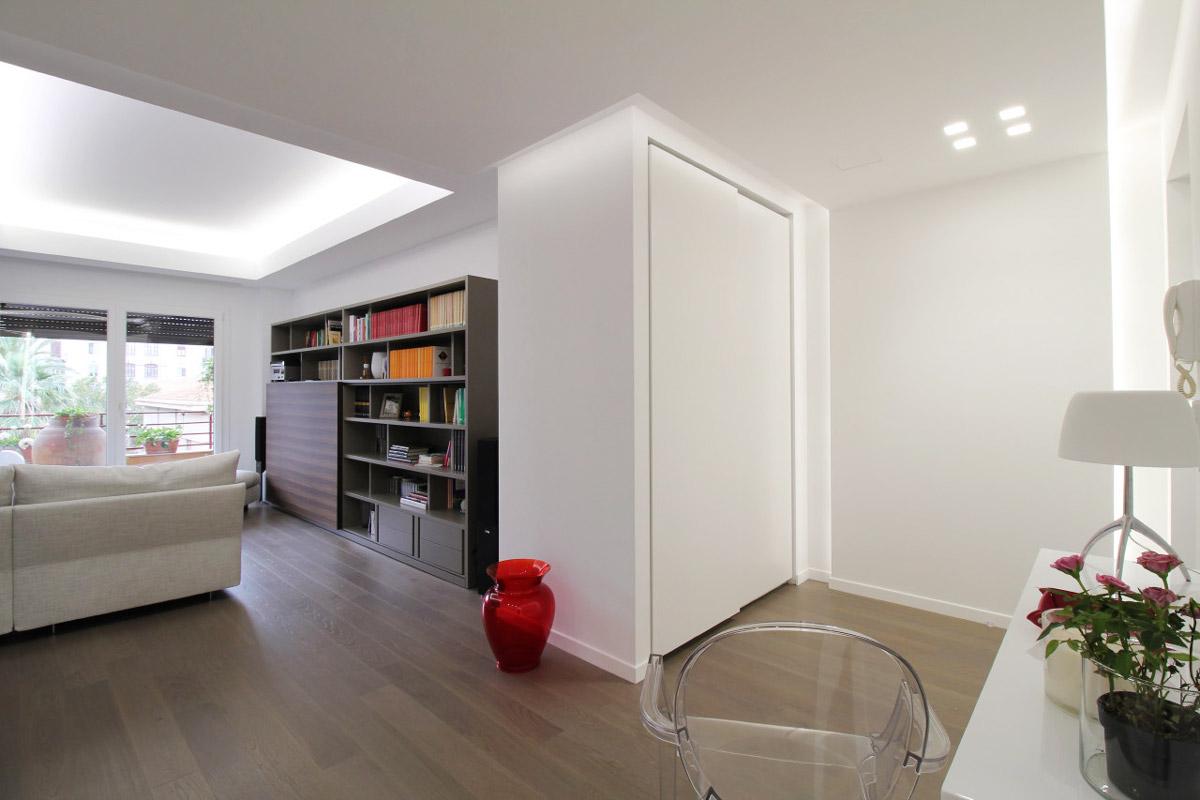 Soggiorno con divano e libreria a parete che da all'ingresso