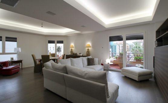 Soggiorno e zona pranzo open space con un divano grigio al centro