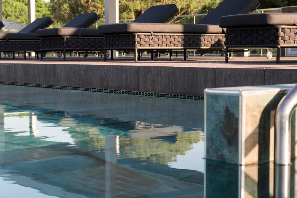 Lettini sdraio marroni su bordo piscina
