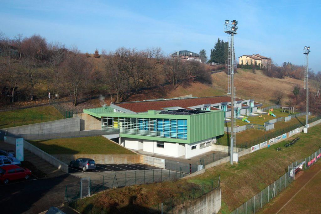 Foto panoramica dell'asilo ubicato su una collina a fianco di un campo da calcio