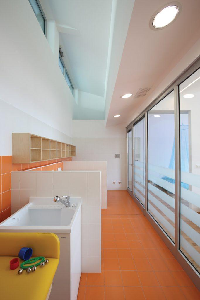 Lavabi a parete lungo un corridoio con alle spalle una vetrata