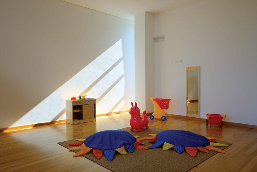Aula con dei giochi e dei cuscini colorati al centro