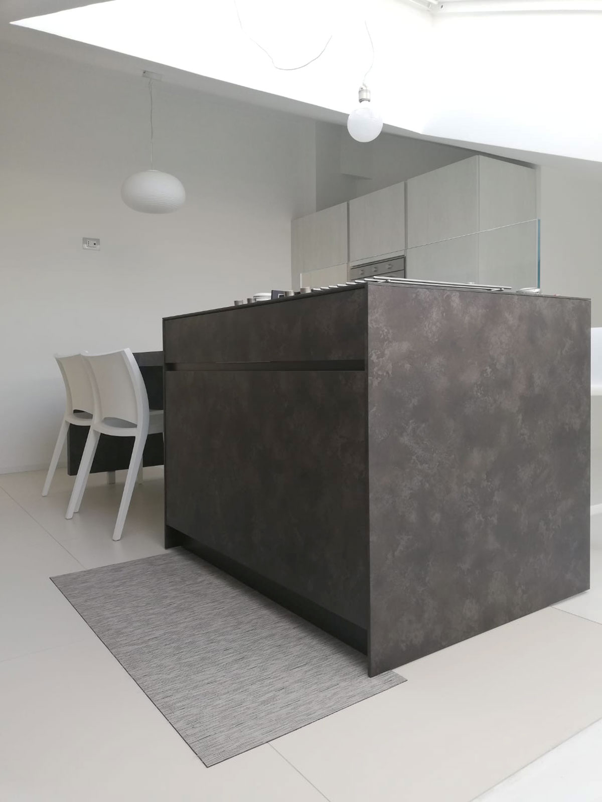 Isola cucina color grigio antracite e sedie di color bianco