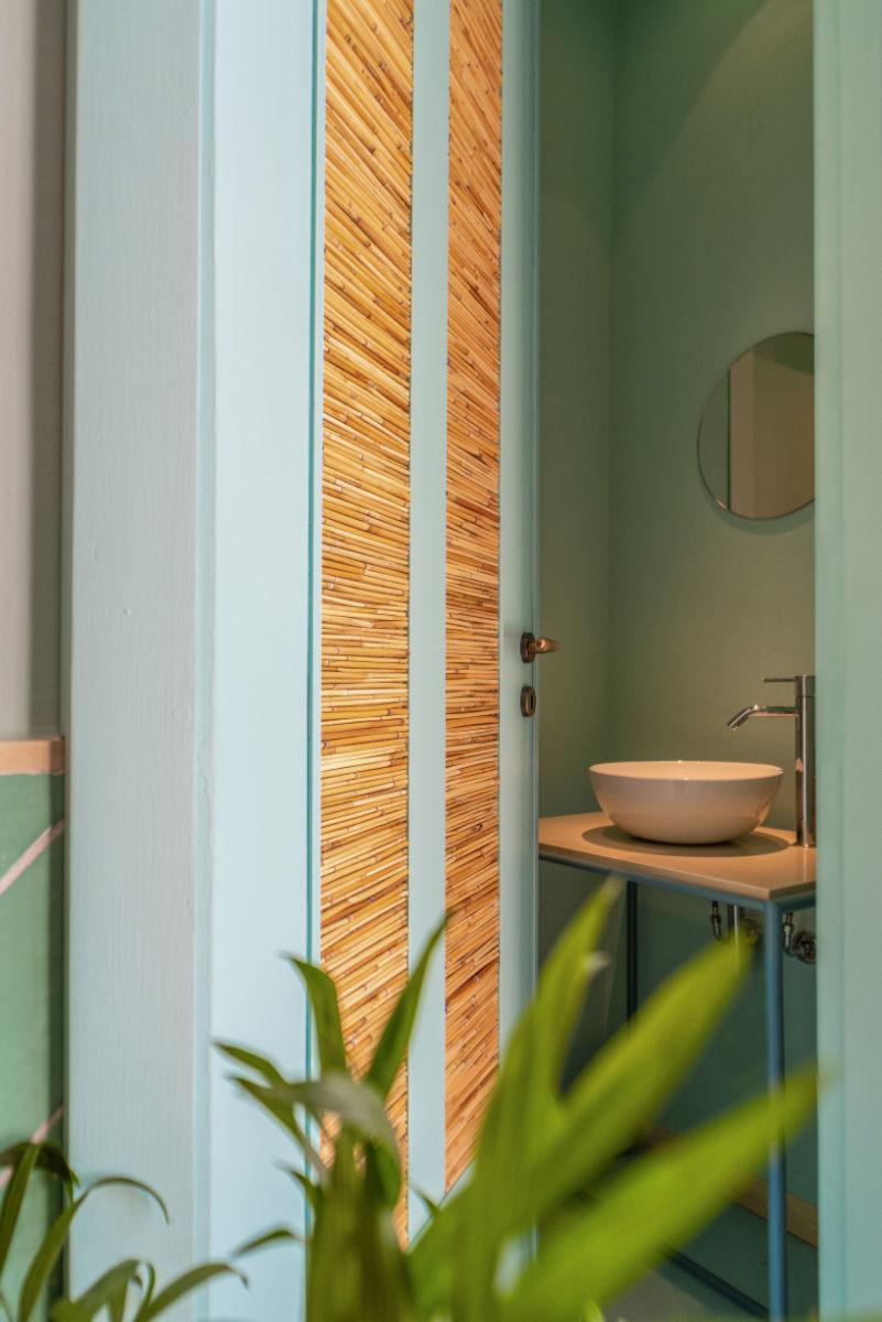 Porta del bagno in legno azzurra che mostra il lavabo