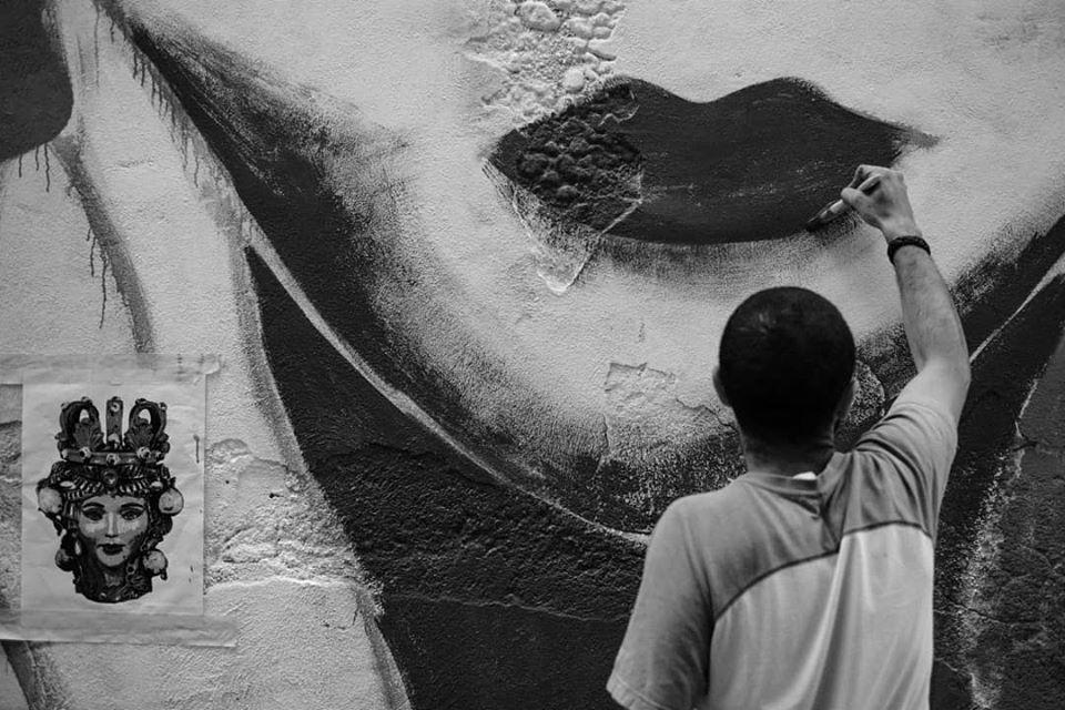 Murales con un ragazzo che disegna delle labbra
