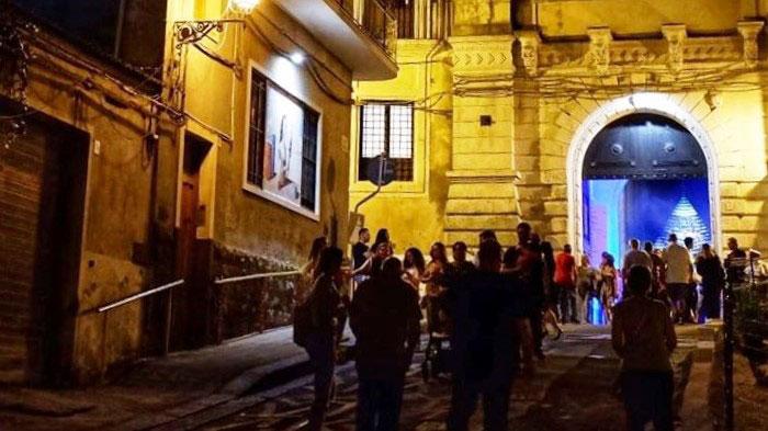 Persone lungo una via durante la sera