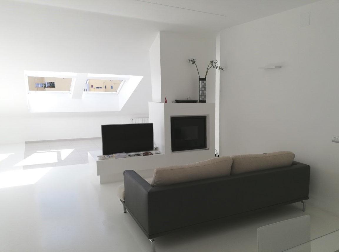 Salotto con camino, televisione e di fronte un divano in pelle nero