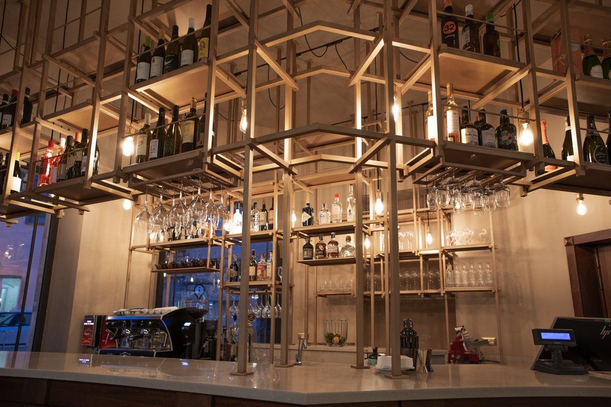 Bancone del locale con una struttura in legno che sorregge le varie bevande