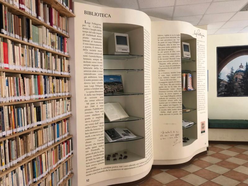 Libreria con in fondo un enorme libro al posto del muro