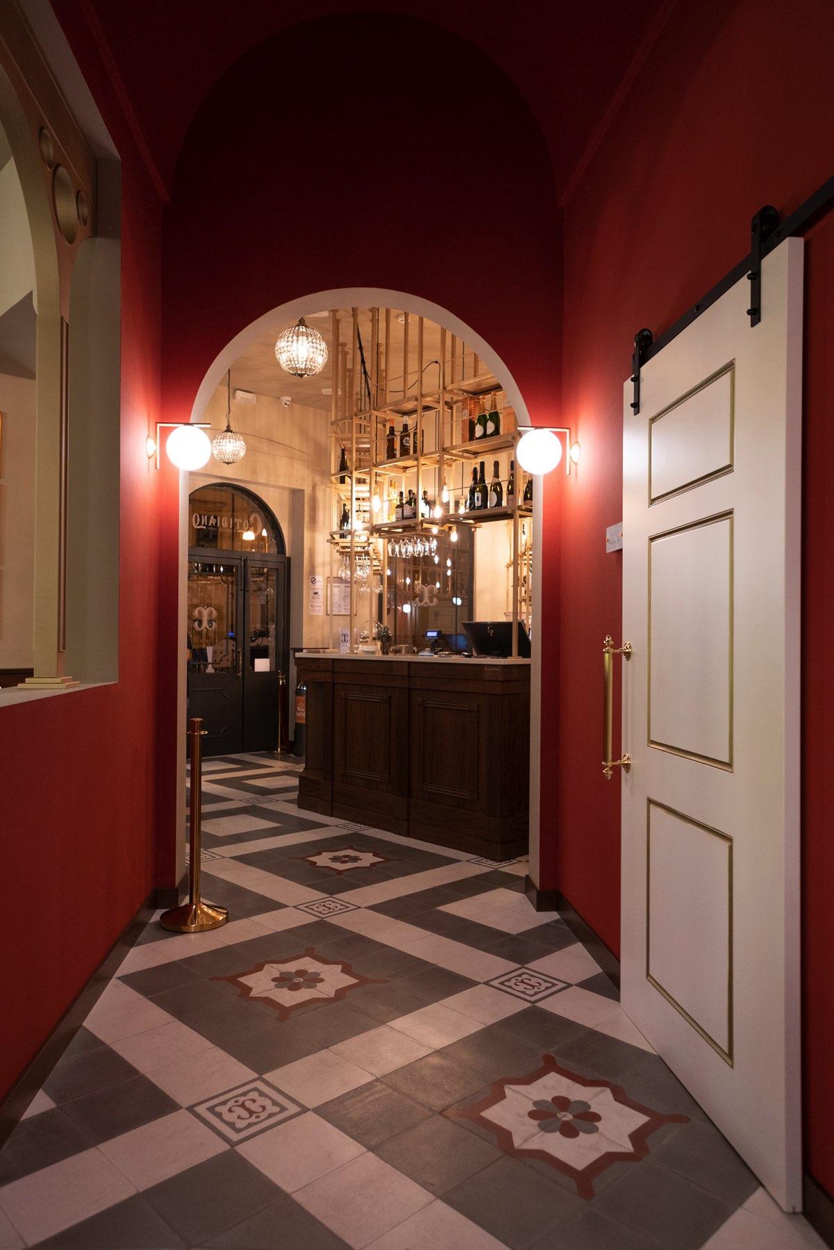 Entrata del locale con pareti rosse ed un archetto sul corridoio