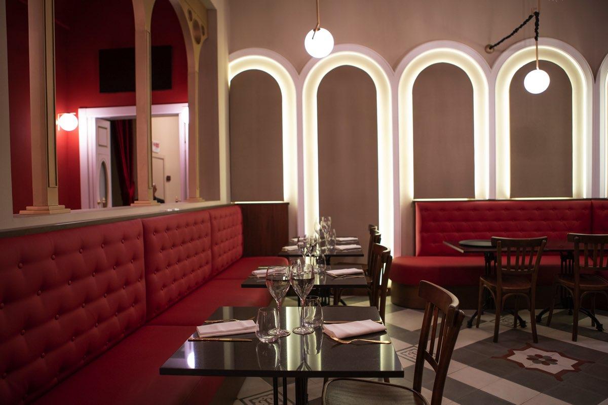 Tavoli neri del locale con sedie in legno e divani in pelle rossa
