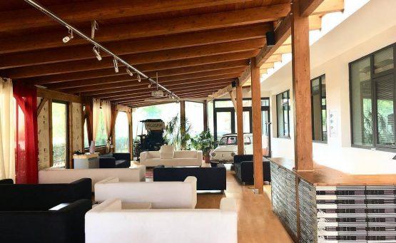 Terrazzo con tettoia in legno e vari divani bianchi e neri