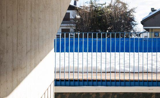 Ringhiera blu che corre lungo una terrazza con una pavimentazione in legno coperta di neve
