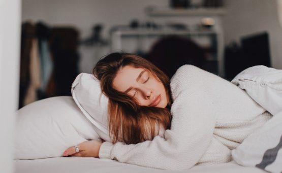 Ragazza che dorme su un letto bianco