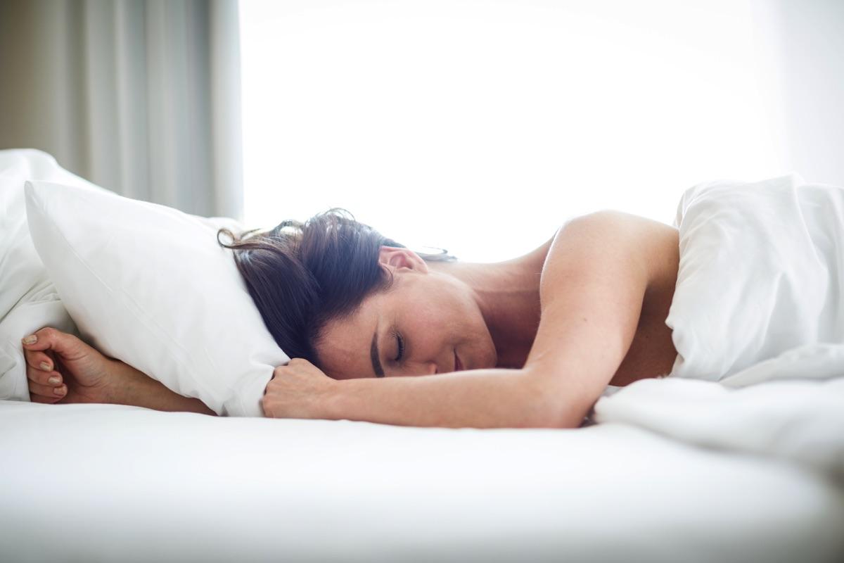 Donna che dorme su delle lenzuola bianche