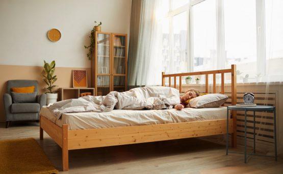 Ragazza dorme su un letto in legno